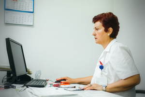 Nurse writing on computer